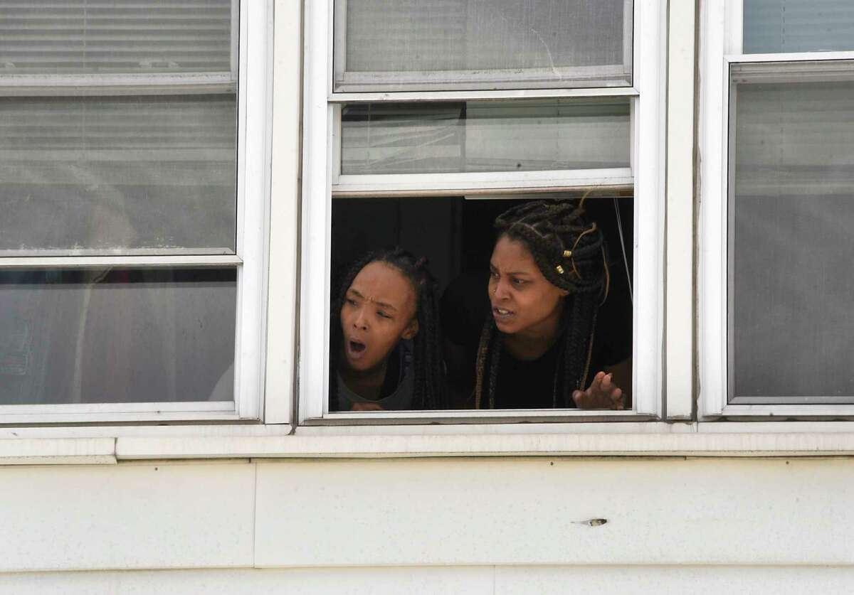 A couple people watch from their upstairs window as teachers and staff from Sheridan Preparatory Academy drive in a parade to show how much they miss their students on Friday, April 17, 2020 in Albany, N.Y. (Lori Van Buren/Times Union)