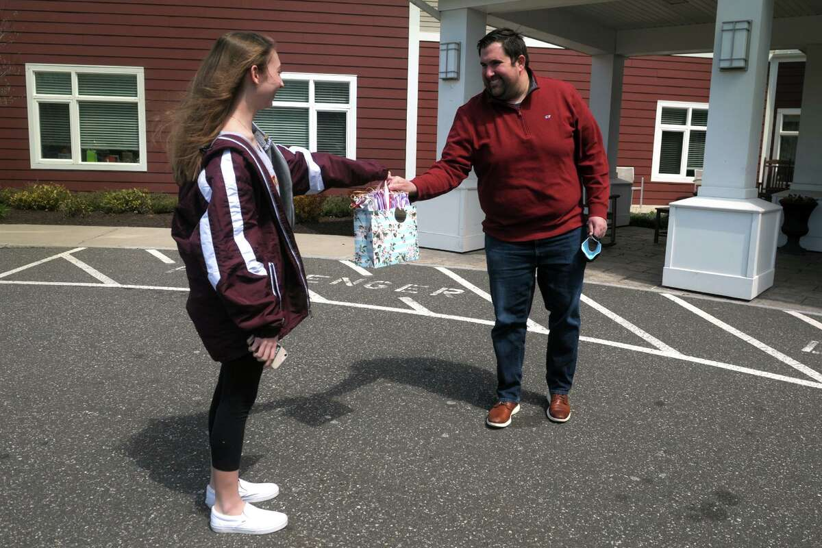 Grace DeDonato, of Shelton, delivers a bag of her home sewn face masks to David Fife, executive director of Benchmark Senior Living at Split Rock, in Shelton, Conn. April 16, 2020. DeDonato has sewn and donated hundreds of her masks to several local hospitals and medical facilities.