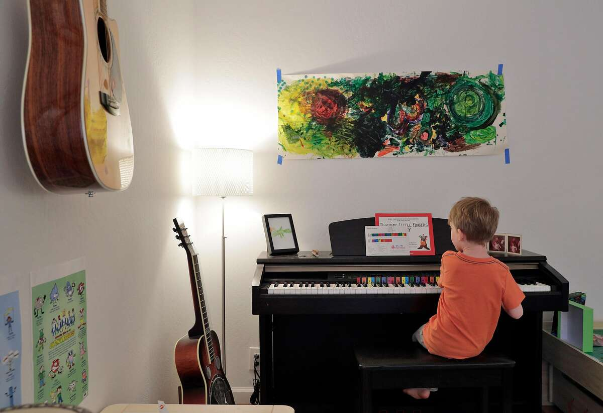 """Alistair, 5, taps out, """"Happy Birthday"""" on the piano (he will celebrate his birthday during shelter in place) before lunch with the Hart family in their home in Pacifica, Calif., on Wednesday, April 15, 2020. Alexa and Ted, she a teacher and he a data scientist, are balancing work and parenting of their two kids, Alistair, 5, and Eloise, 2, during Covid-19 shelter in place precautions."""