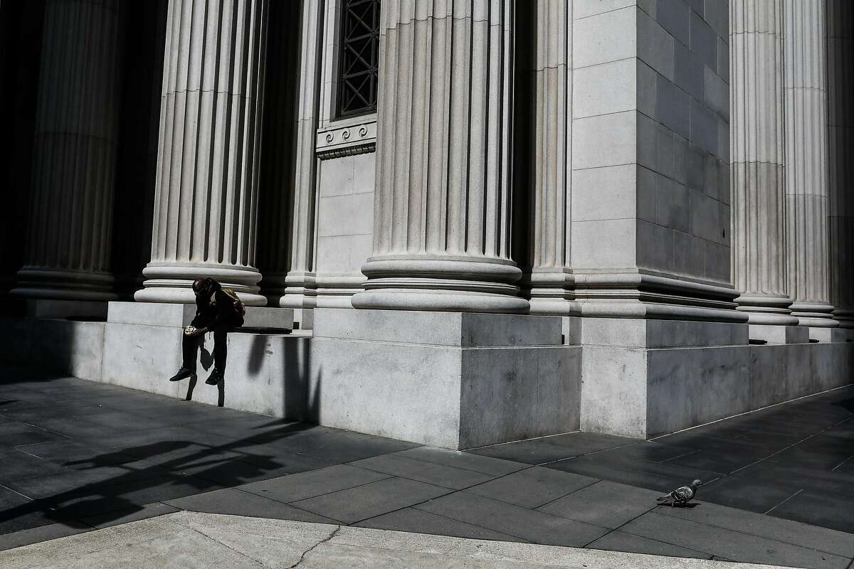 A person eats outside in the financial district on Tuesday, March 17, 2020 in San Francisco, California. The city is on lockdown due to the coronavirus.