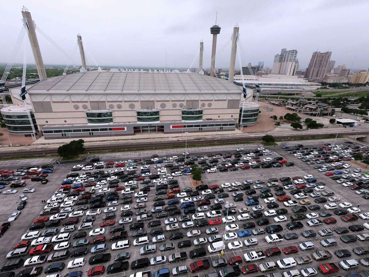 People in their vehicles line up for the Food Bank's distribution Friday at the Alamodome. The Food Bank aided about 10,000 households in a record-setting giveaway held April 9 at a South Side flea market.