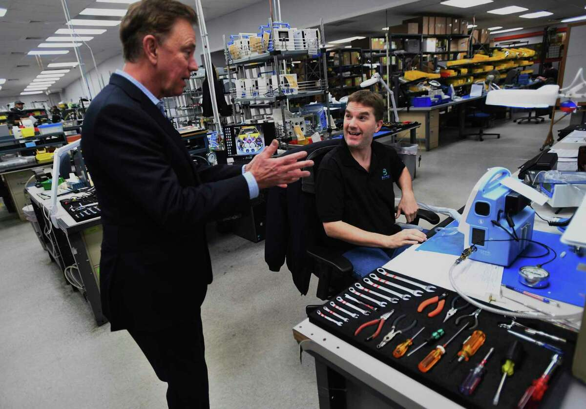 Governor Ned Lamont, left, talks with Service Manager Keith Wilson during a tour of ventilator manufacturer Bio-Med Devices in Guilford.