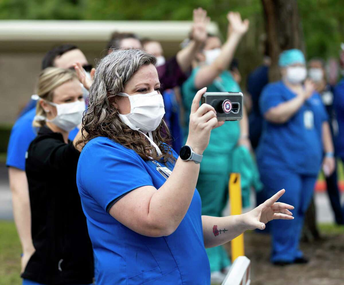 A staff member of HCA Houston Healthcare Conroe takes video footage of a drive-by parade.