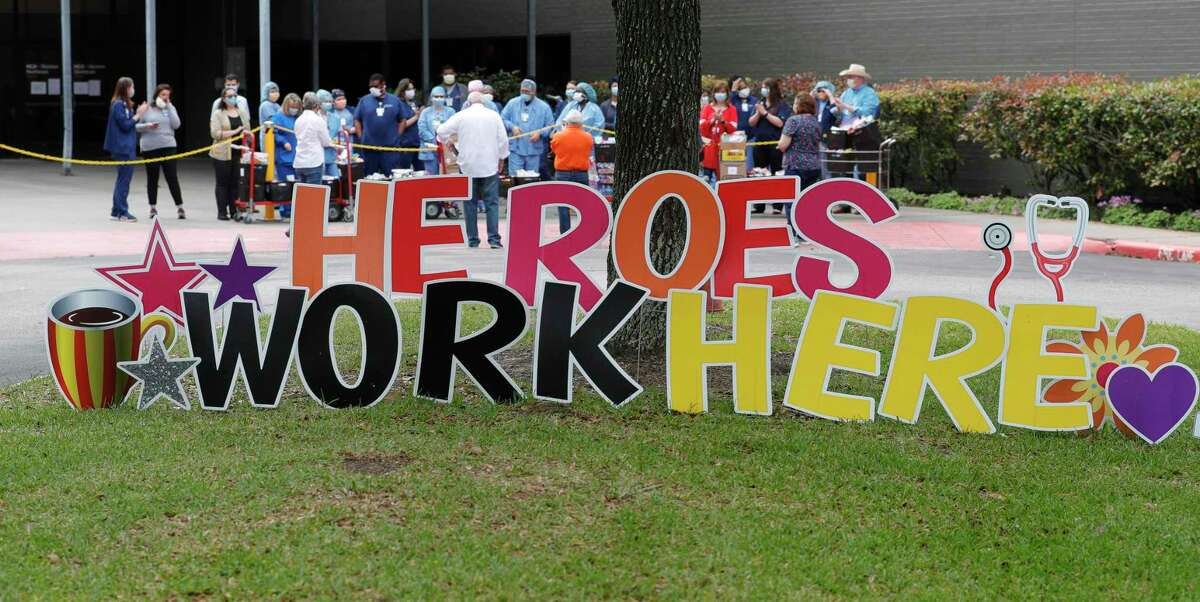 """A sign that says """"Heroes Work Here"""" is seen as members of West Conroe Baptist Church delivered care packages to medical personnel at HCA Houston Healthcare Conroe, Friday, April 17, 2020, in Conroe."""