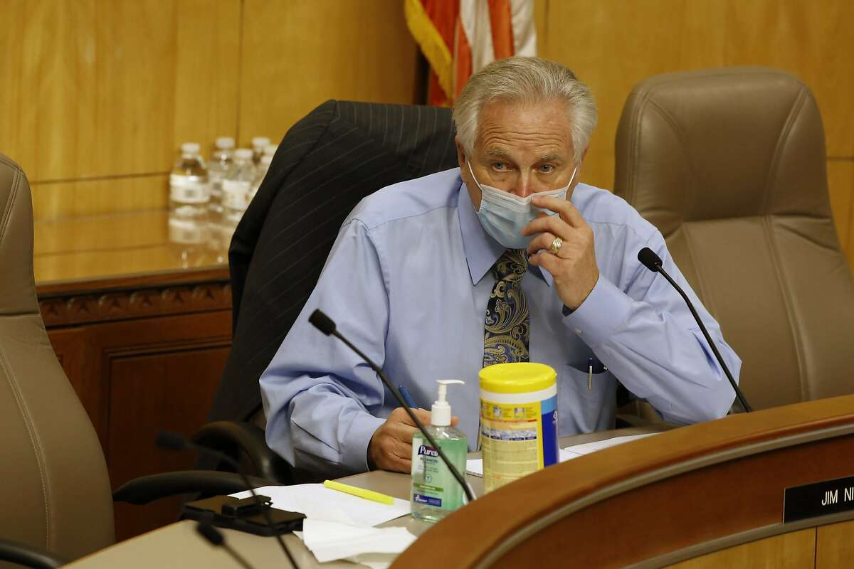 State Sen. Jim Nielsen, R-Gerber, vice chair of senate budget committee, adjusts his face mask during a hearing of the special subcommittee on COVID-19, at the Capitol in Sacramento, Calif., Thursday, April 16, 2020. Lawmakers are looking into how Gov. Gavin Newsom has been spending money to address the new coronavirus crisis. Following safety guidelines everyone attending the hearing wore face masks and were to maintain social distancing. (AP Photo/Rich Pedroncelli, Pool)
