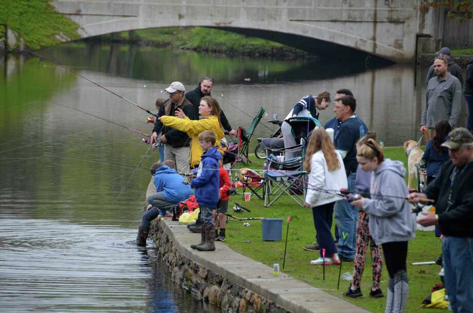 A group of young anglers surround Kurt Schutz on May 4, 2019, during the Milford Striped Bass Club's annual Children's Trout Derby. The children with him include his son, Lance, and a group of others who were trying to recapture a fish that has slipped back into the water. This year's derby has been canceled due to the novel Coronavirus. Photo: File Photo