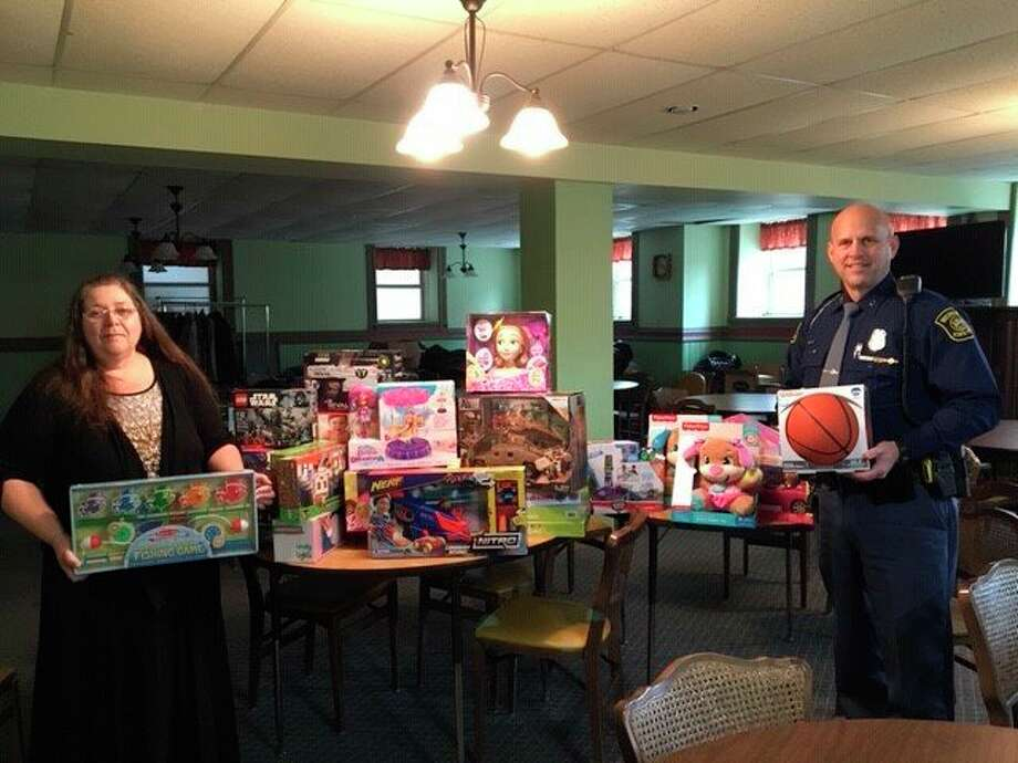 Michigan State Police Trooper David Prichard delivers toys to Lisa Clarke, family services director of ECHO His Love, for the Family Life Center. (File photo)