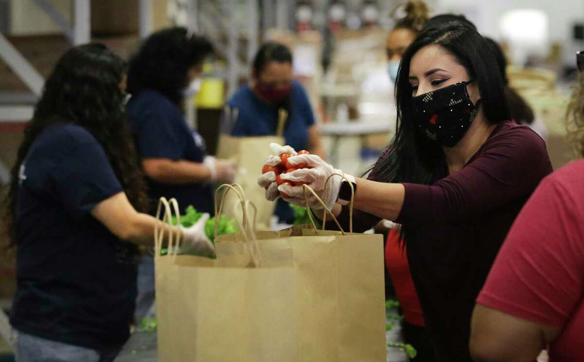 Kimberly Cuevas, right, and other volunteers from Pre-K 4 SA load bags with produce at the San Antonio Food Bank as trucks are loaded Thursday, April 16, 2020, in preparation for emergency food distribution at the Alamodome on Friday. Before COVID-19, the organization fed 58,000 households per week. Now, it is supplying free groceries to 120,000 per week.