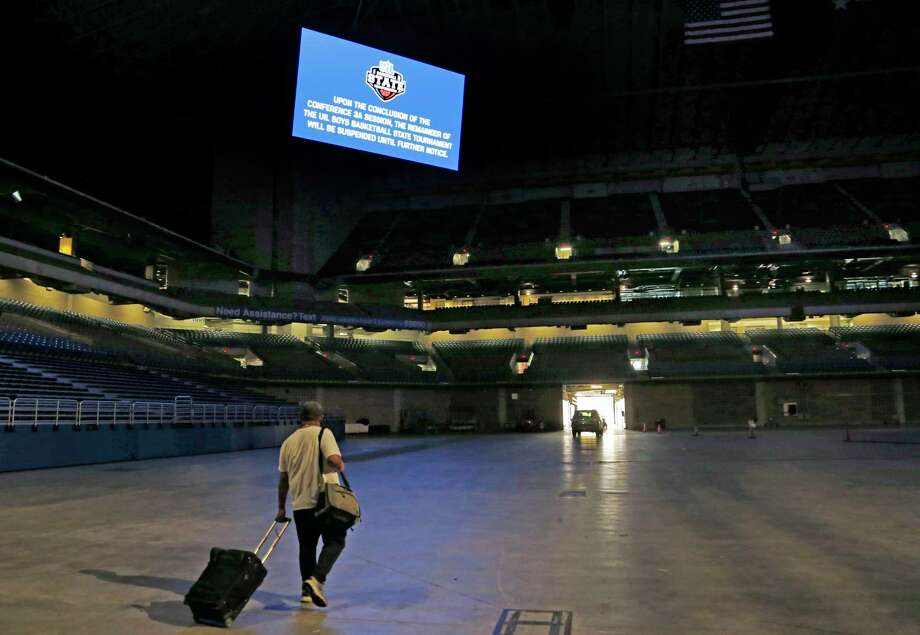 A media member leaves the arena a sign reminds that the rest of the boy's state basketball tournament is postponed, Thursday, March 12, 2020, at the Alamodome in San Antonio. Officials have decided to postpone the tournament after the Thursday afternoon session for Class 3A schools. The University Interscholastic League, which governs extracurricular activities in Texas' public schools, said it made the call due to growing concerns about the COVID-19 virus. (Ron Cortes/The Dallas Morning News via AP) Photo: Ron Cortes, MBR / Associated Press / 2020 Ronald Cortes