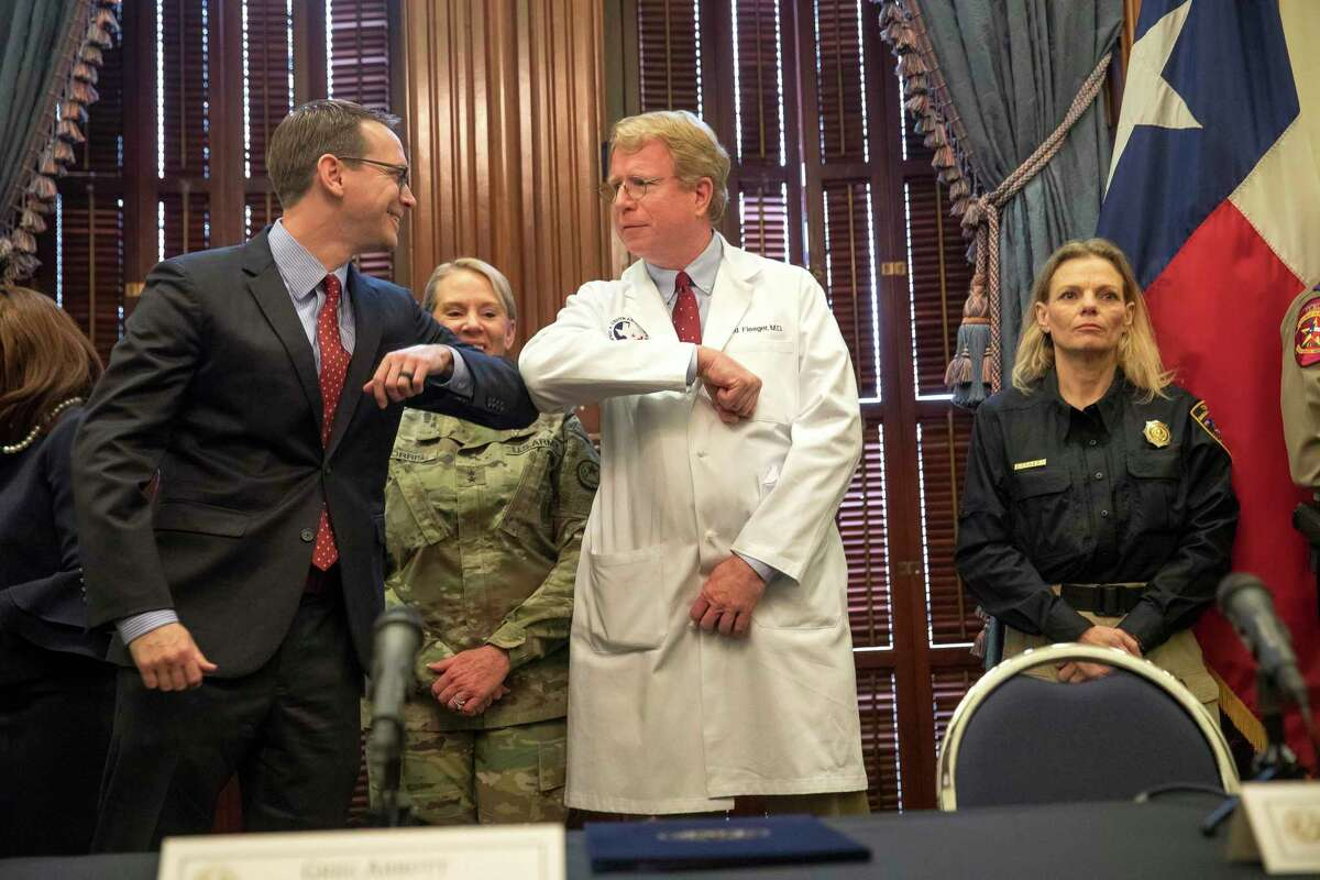 Texas Education Agency Commissioner Mike Morath, left, and Dr. David Fleeger, right, greet each other with an elbow touch before the start of a press conference on the coronavirus by Governor Greg Abbott at the Texas State Capitol in Austin, Texas on March 13, 2020. The vast majority of people recover from the new coronavirus. According to the World Health Organization, most people recover in about two to six weeks, depending on the severity of the illness. (Julia Robinson/The Dallas Morning News via AP)