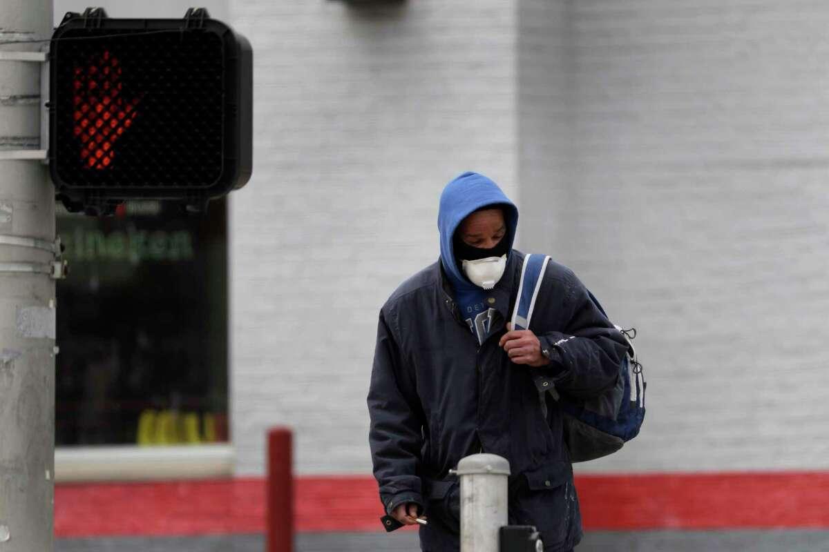 A man wears a protective mask as he waits to cross a street.