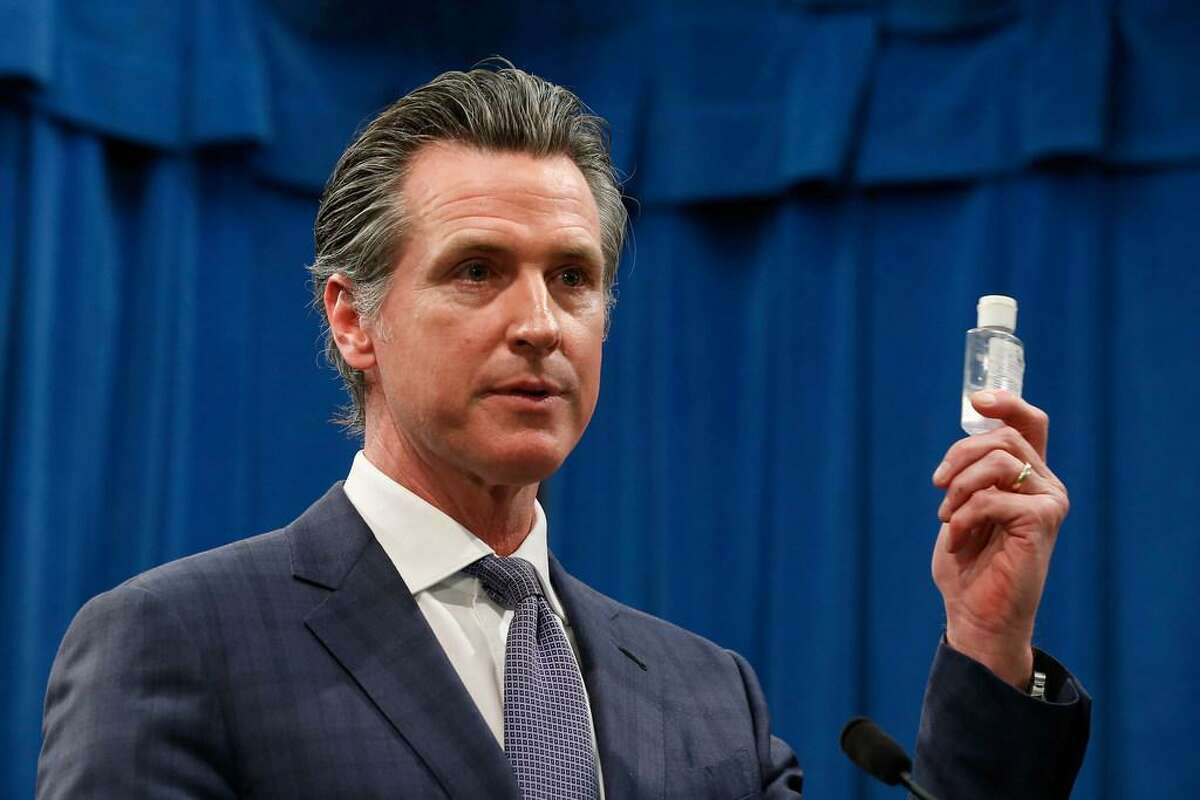 California Gov. Gavin Newsom displays a bottle of hand sanitizer while saying the state would take action against price gouging because of the coronavirus, at a Capitol news conference in Sacramento, Calif., Wednesday, March 4, 2020.
