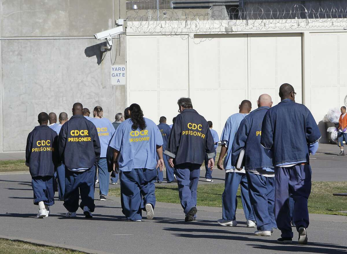 Inmates walk through the exercise yard at California State Prison Sacramento near Folsom. Gov. Gavin Newsom's proposed budget would close two state prisons over the next three years.