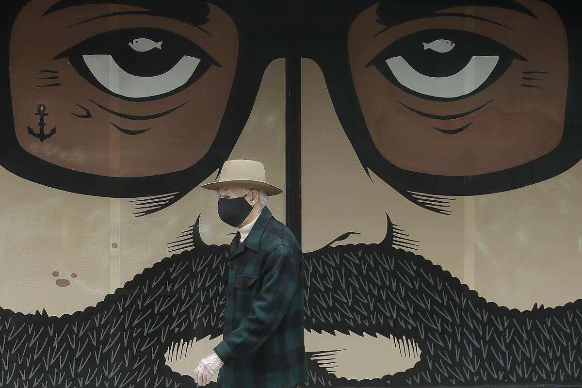 A man wears a mask while walking in front of a closed building in San Francisco, Thursday, April 16, 2020. (AP Photo/Jeff Chiu)