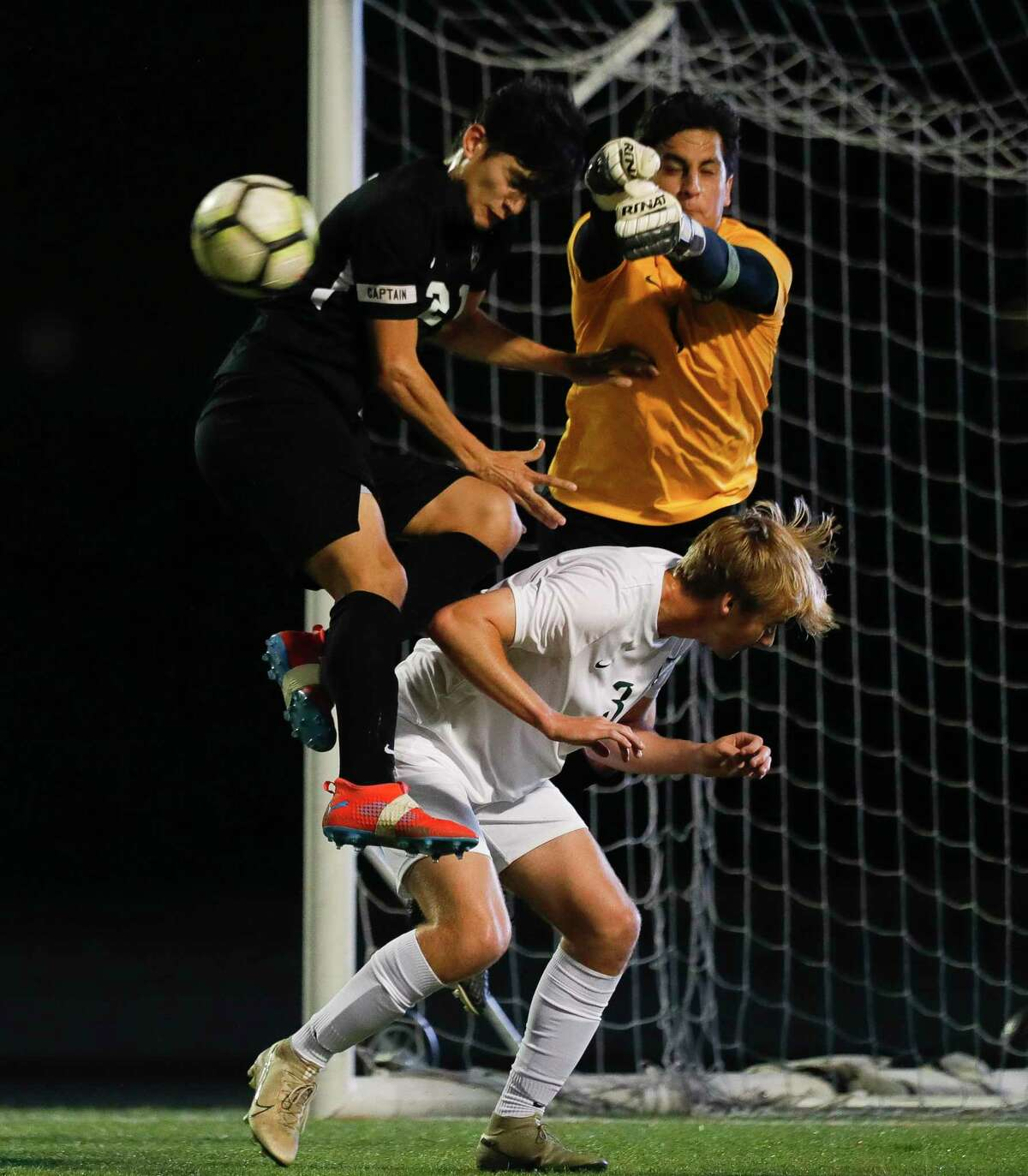 Conroe's Luis Zamora (21) tries to connect on a header by Josue Fuentes as The Woodlands goalie Eddy Tenorio (1) breaks up the ball during the first period of a District 15-6A high school soccer match at Buddy Moorhead Stadium, Tuesday, March 10, 2020, in Conroe.