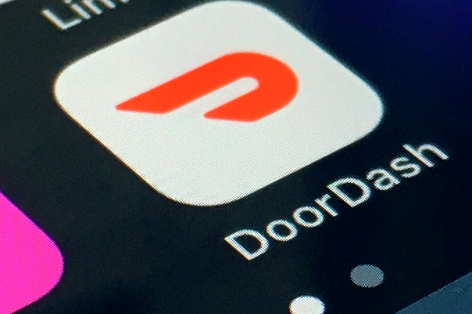 """FILE - In this Feb. 27, 2020, file photo, the DoorDash app is shown on a smartphone in New York. Some app-based delivery companies have announced hiring sprees to cope with a surge in orders from millions of people stuck at home. DoorDash has launched a """"priority access program"""" to help laid off restaurant employees sign up for delivery work. (AP Photo, File) / ap"""