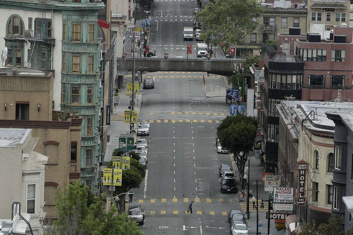 A pedestrian crosses a nearly empty Kearny Street in San Francisco, Thursday, April 16, 2020. (AP Photo/Jeff Chiu)