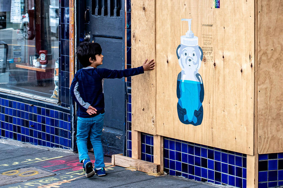 A child reaches out towards one of fnnch's bears, although it's no substitute for a bottle of Purell.