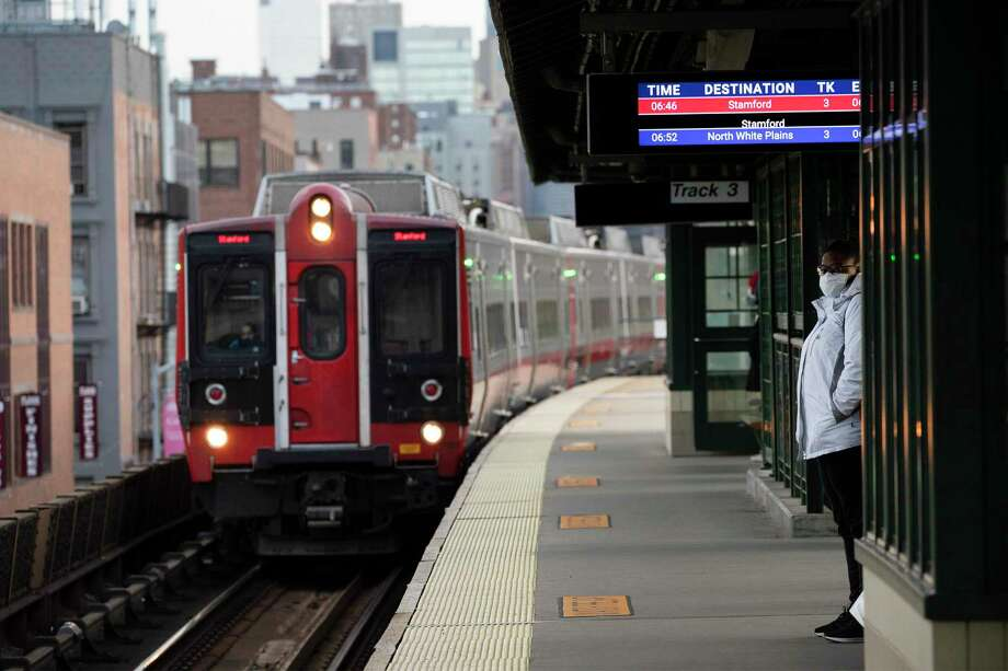A woman wearing a mask waits for a train on a Metro-North Railroad platform at the 125th Street train station in New York state recently. You are now required to wear a face mask when riding trains on the Metropolitan Transportation Authority's Metro-North Railroad rail lines in the states of New York, and Connecticut. (AP Photo/Mark Lennihan) Photo: Mark Lennihan / Associated Press / Copyright 2020 The Associated Press. All rights reserved