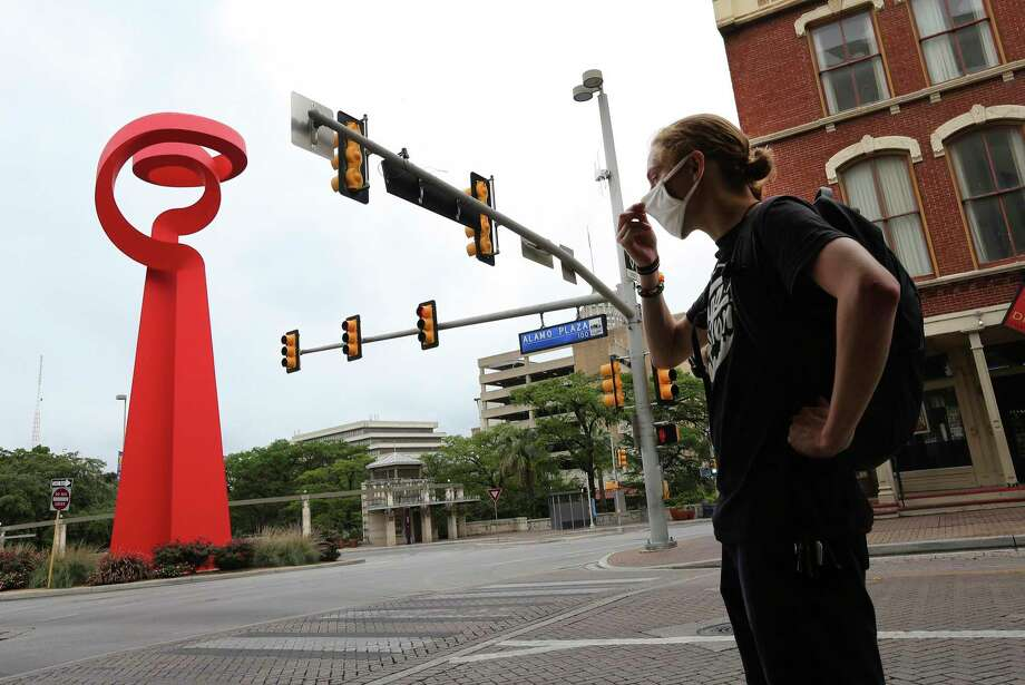 Liam Price adjusts his mask after a bike ride through downtown near the Torch of Friendship statue along Alamo Plaza and Commerce Streets in downtown on Friday. Photo: Kin Man Hui, San Antonio Express-News / Staff Photographer / **MANDATORY CREDIT FOR PHOTOGRAPHER AND SAN ANTONIO EXPRESS-NEWS/NO SALES/MAGS OUT/ TV OUT