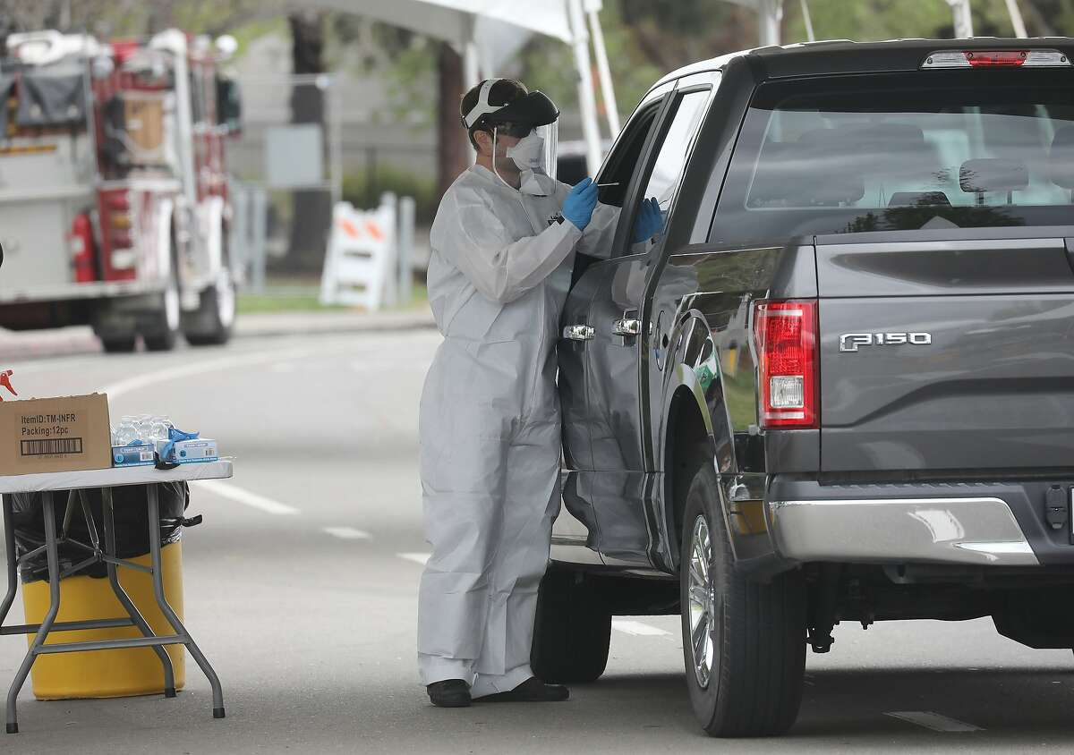 A medical worker prepares to test for COVID-19, the disease caused by the coronavirus, at a drive-thru testing site in Hayward, Calif., Monday, April 12, 2020. (Jim Wilson/The New York Times)