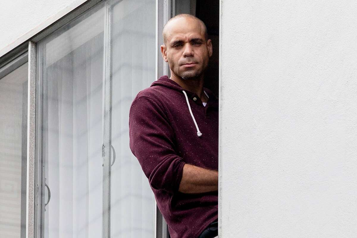 Darius Banks, 46, poses for a portrait in the window of his hotel room in San Francisco, Calif. Thursday, April 16, 2020. Thousands of homeless people are being moved out of shelters and streets and into leased hotel rooms during the Coronavirus outbreak.