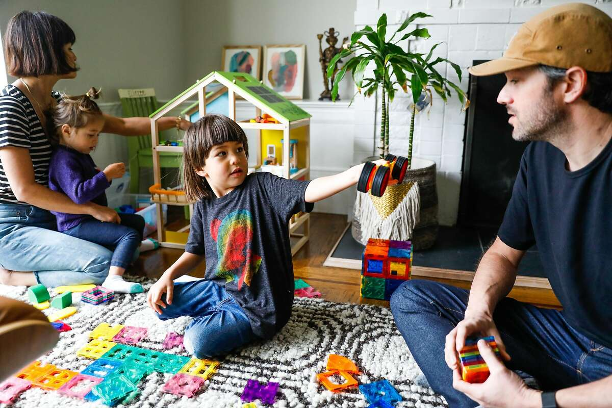 Jenny Seeger (left) and her husband Chad Seeger (right) play with their kids Eliette, 2, Graham, 4 (center) in their living room on Thursday, April 16, 2020 in San Francisco, California. Before the shelter in place took effect due the the coronavirus the Seeger�s used to only allow their children 30-minutes of screen time. Now that they are working from home in quarantine they�ve had to extend the use of iPad�s and television to several hours to get their work done.