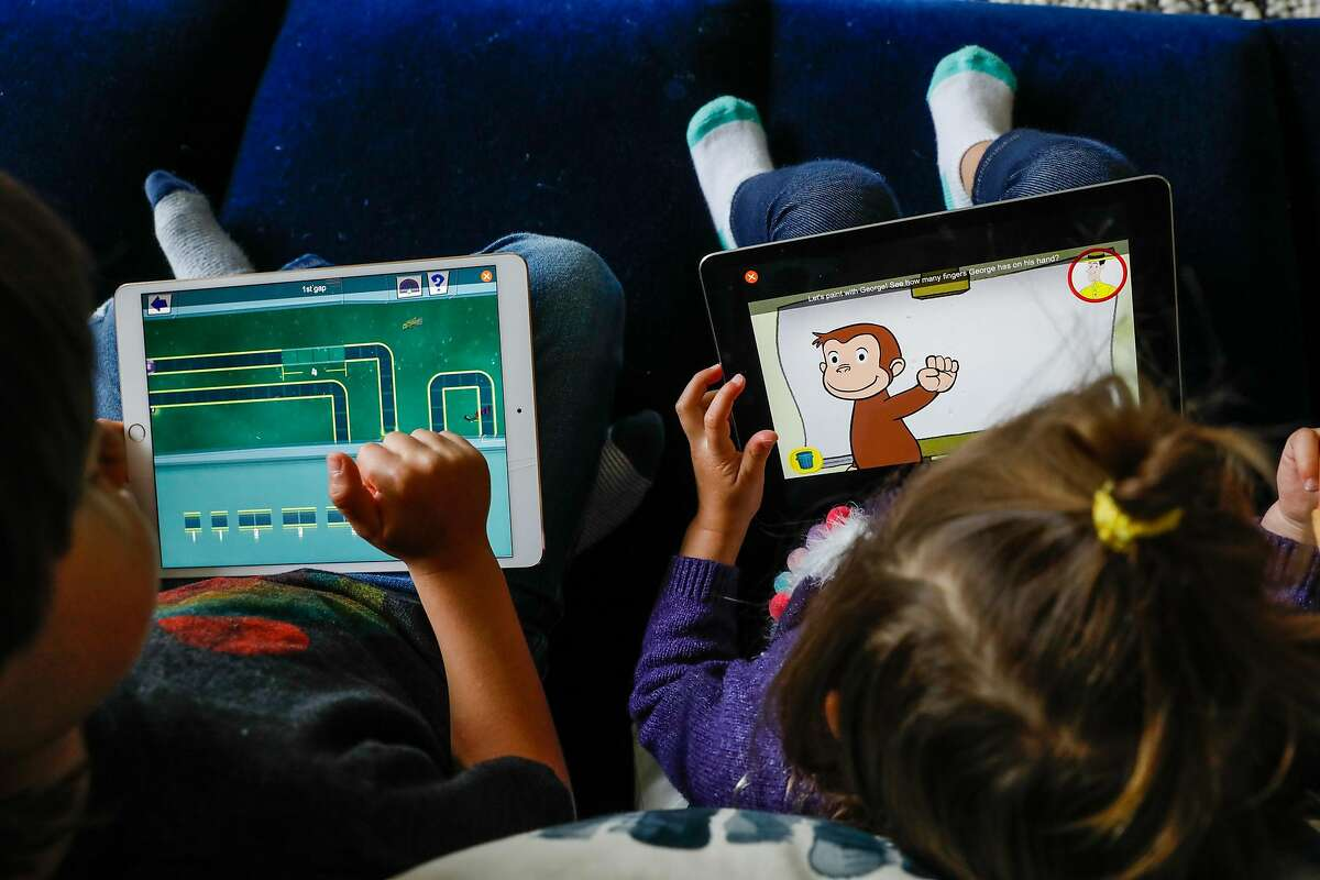 (L-r) Graham Seeger, 4, and sister Eliette Seeger, 2, relax on their iPads so that their parents can get work done on Thursday, April 16, 2020 in San Francisco, California. Before the shelter in place took effect due the the coronavirus the Seeger�s used to only allow their children 30-minutes of screen time. Now that they are working from home in quarantine they�ve had to extend the use of iPad�s and television to several hours to get their work done.