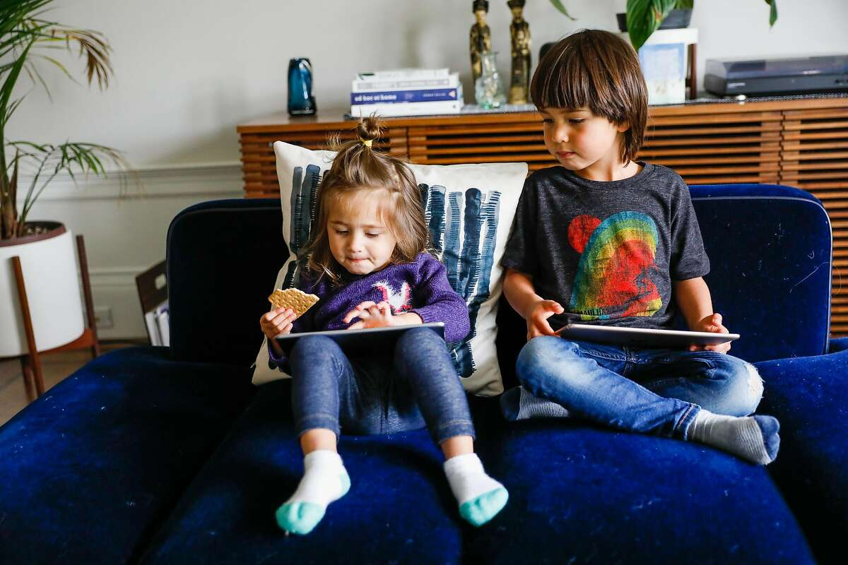 (L-r) Eliette Seeger, 2, and her brother Graham Seeger,4, relax on their iPads so that their parents can get work done on Thursday, April 16, 2020 in San Francisco, California. Before the shelter in place took effect due the the coronavirus the Seeger�s used to only allow their children 30-minutes of screen time. Now that they are working from home in quarantine they�ve had to extend the use of iPad�s and television to several hours to get their work done.