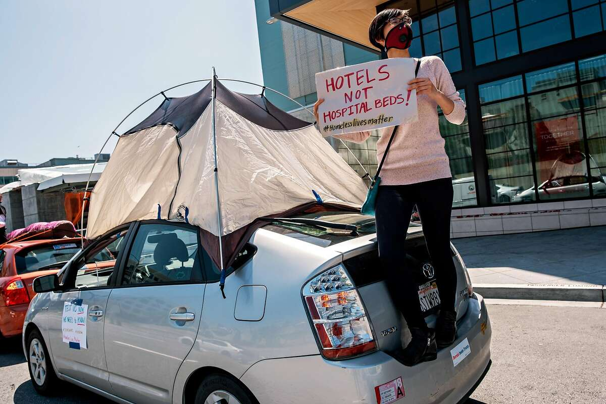 Protester Emily Lee is seen holding a sign while standing on her car after a car convoy of about 50 drove by the Moscone Center to demand shelter for the homeless in San Francisco, Calif. on Monday April 13, 2020.