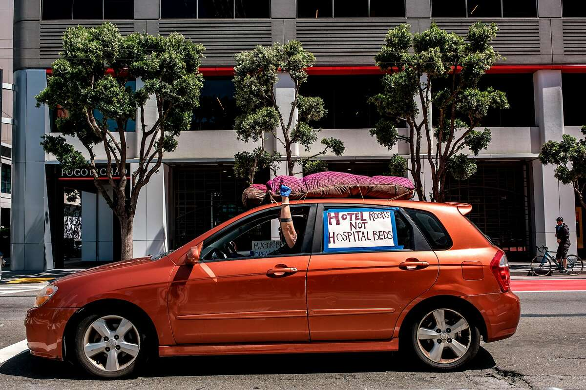 A protester is seen in the car as a car convoy of about 50 drives by the Moscone Center to demand shelter for the homeless in San Francisco, Calif. on Monday April 13, 2020.