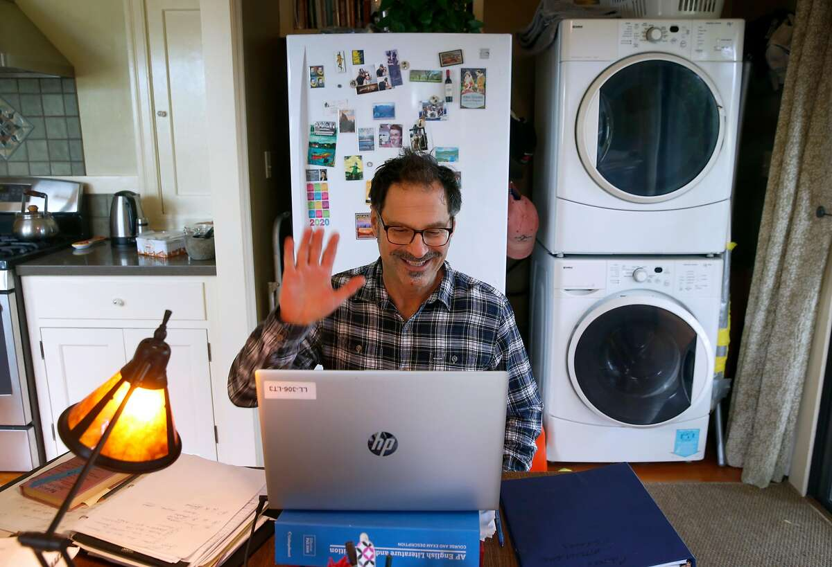Will Cautero waves to Las Lomas High School students as they log in for an 11th grade English class conducted remotely from his home in Oakland, Calif. on Thursday, April 16, 2020.