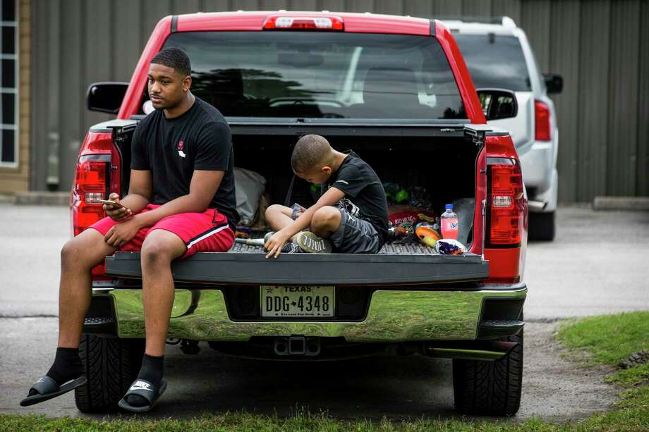 Chauncey Phillips, a sophomore at Beaumont Westbrook, and fourth grader Trovon Morgan sit in the back of a pickup waiting for their veterinarian to open on Friday, April 17, 2020 in Conroe. The boys will not return to in person classes at their respective schools after Gov. Greg Abbott announced Friday that public and private school classrooms will remain closed for the remainder of the school year to avoid quickening the spread of COVID-19. The decision, made with the advice of doctors and health officials, came alongside a series of executive orders intended to slowly reopen the state economy, relaxing restrictions on retail businesses, doctor's offices and public parks. Photo: Brett Coomer, Houston Chronicle / Staff Photographer / © 2020 Houston Chronicle