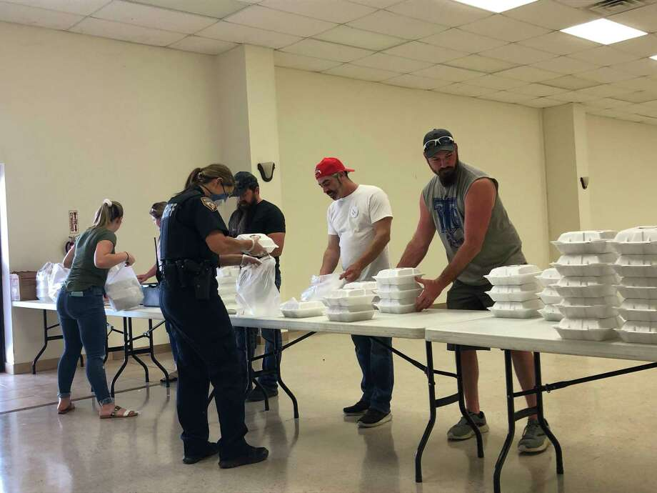Volunteers, including Hungry Jack's Charlie Dahu (second from right in the the backwards red cap) bag and box meals during the Crosby Education Foundation and Hungry Jack meal distribution at the Crosby American Legion Post on April 17. Photo: Elliott Lapin / Staff Photo