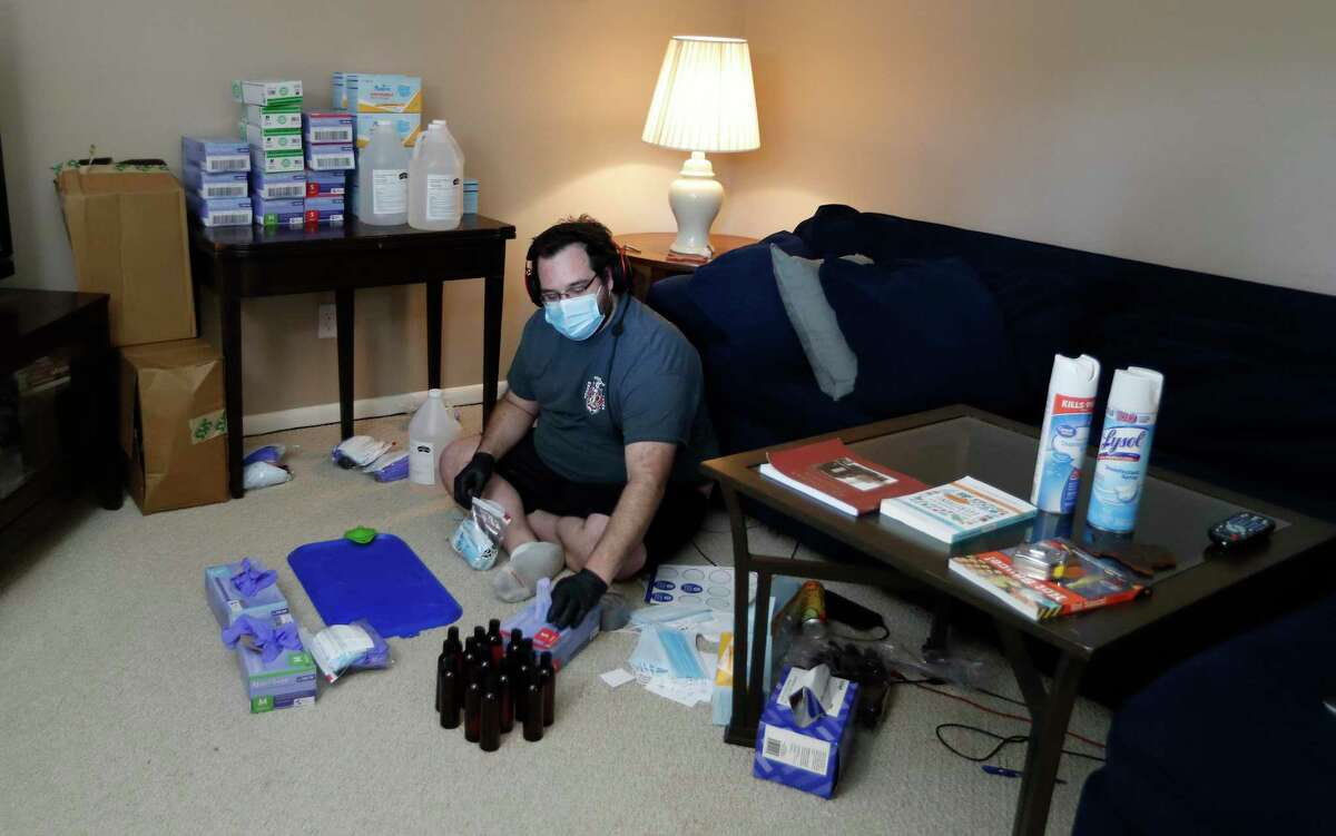 """Matthew Marchetti with CrowdSource Rescue, places PPE in bags for those in need of personal protection equipment in his living room, in Houston,Friday, April 17, 2020. During disasters, CrowdSource Resource hooks up people in trouble to volunteers who can help. """"We're a bunch of tech nerds and response cowboys -- people with chainsaws and boats,"""" says Matthew Marchetti, one of the guys who accidentally started the group during Hurricane Harvey. A pandemic wasn't their sort of crisis. Then they realized that people vulnerable to the coronavirus were going to need food, and nobody was there to deliver it."""