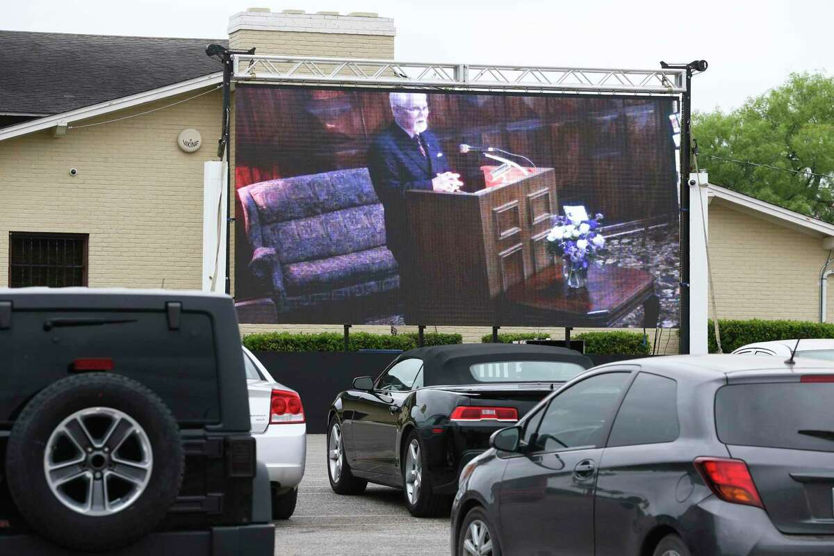 Mission Park Funeral Chapels South conducts a funeral service Friday with a large video screen displaying the services to mourners who stay in their cars in the parking lot.