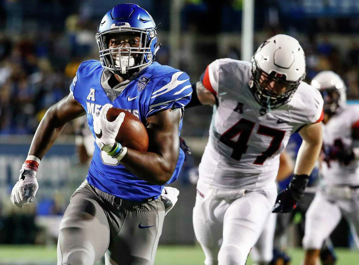 Memphis running back Patrick Taylor Jr., left, runs past Connecticut defender Santana Sterling on his way to a touchdown during an NCAA college football game Saturday, Oct. 6, 2018, in Memphis, Tenn. (Mark Weber/The Commercial Appeal via AP)