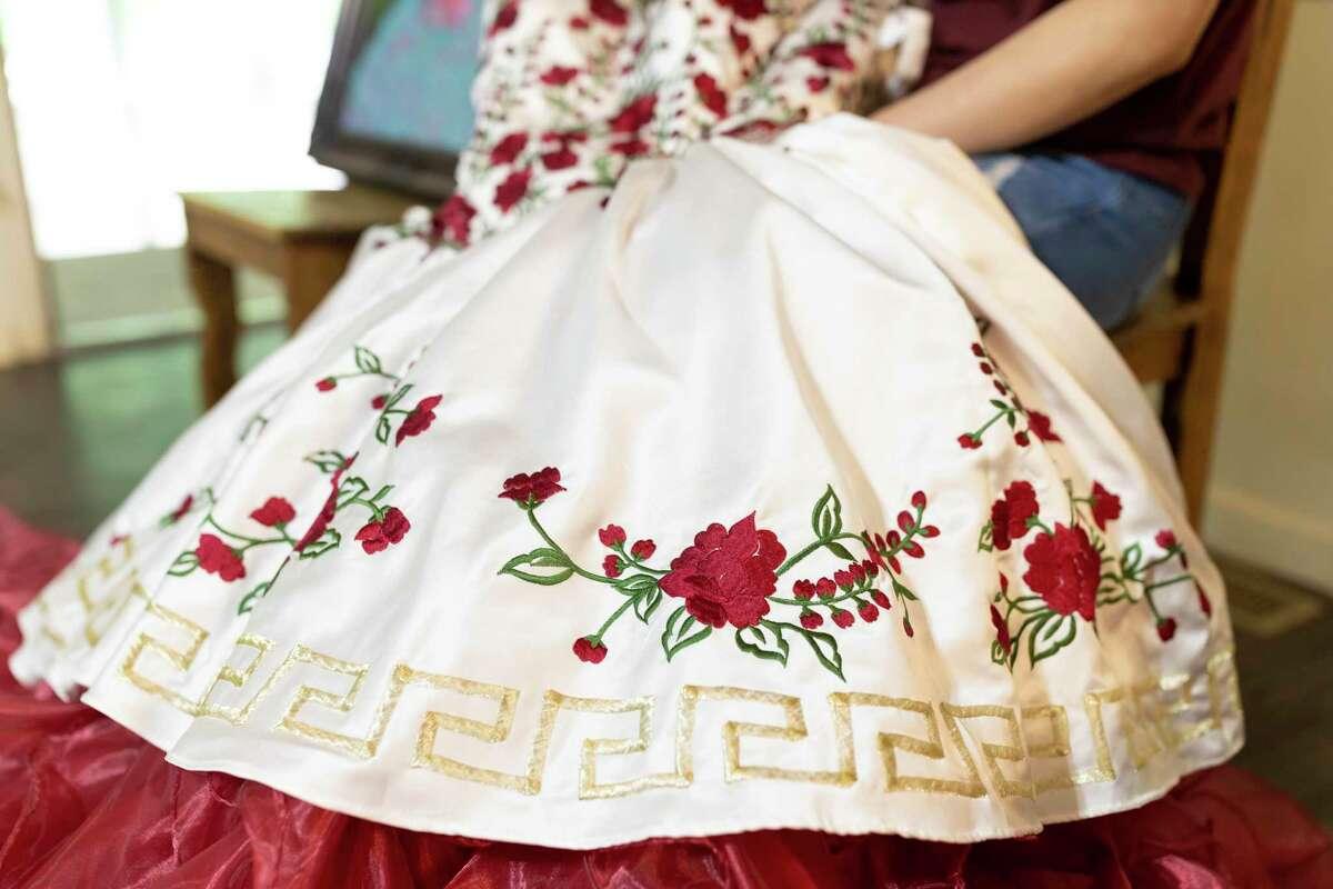 Jamie Rojo holds her quinceañera dress in her home in Willis, Monday, April 6, 2020.