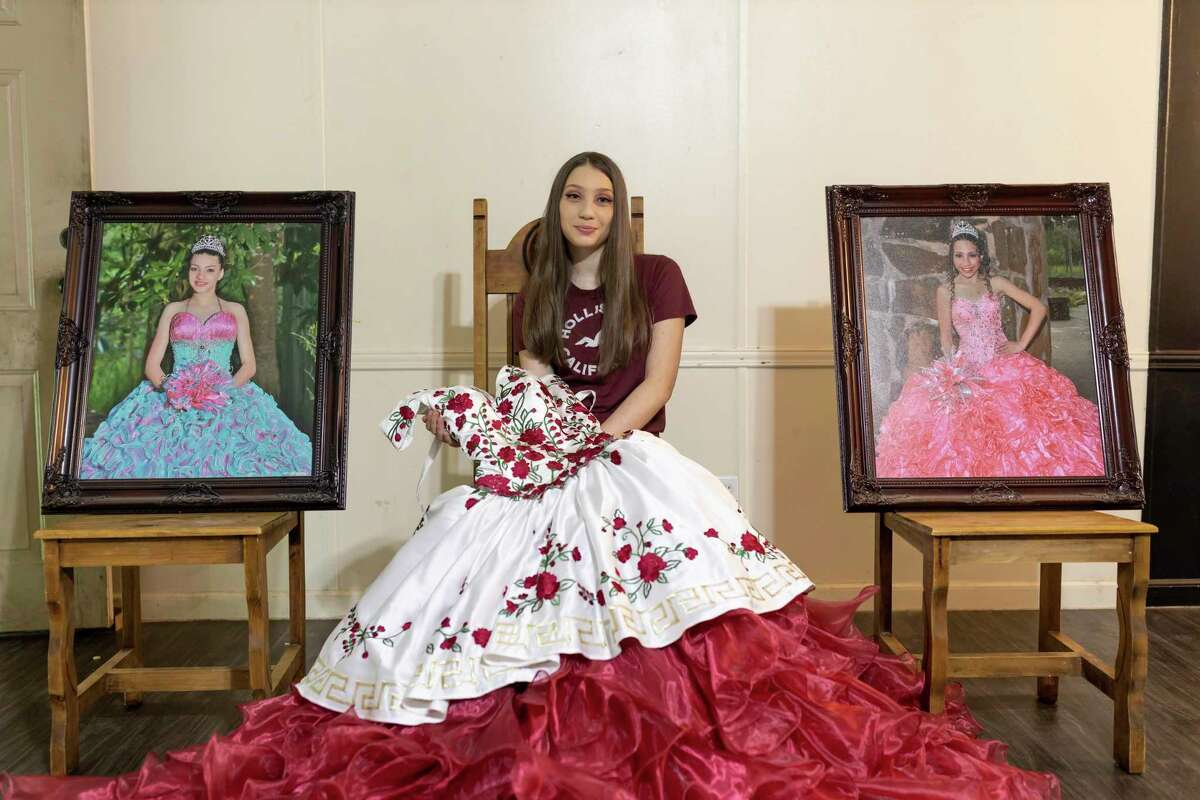 Jamie Rojo poses next to two portraits of her sister's quinceañeras in her home in Willis, Monday, April 6, 2020.