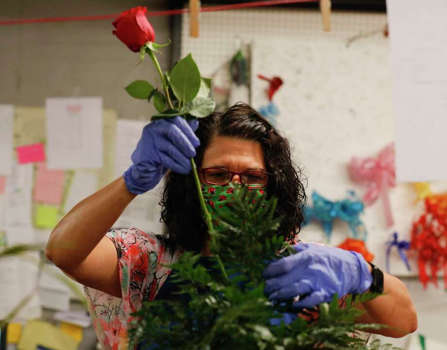 Melissa Vincent places a rose into a funeral arrangement at Heavenly Cakes and Flowers, Friday, April 17, 2020, in Conroe. Photo: Jason Fochtman, Houston Chronicle / Staff Photographer / 2020 © Houston Chronicle