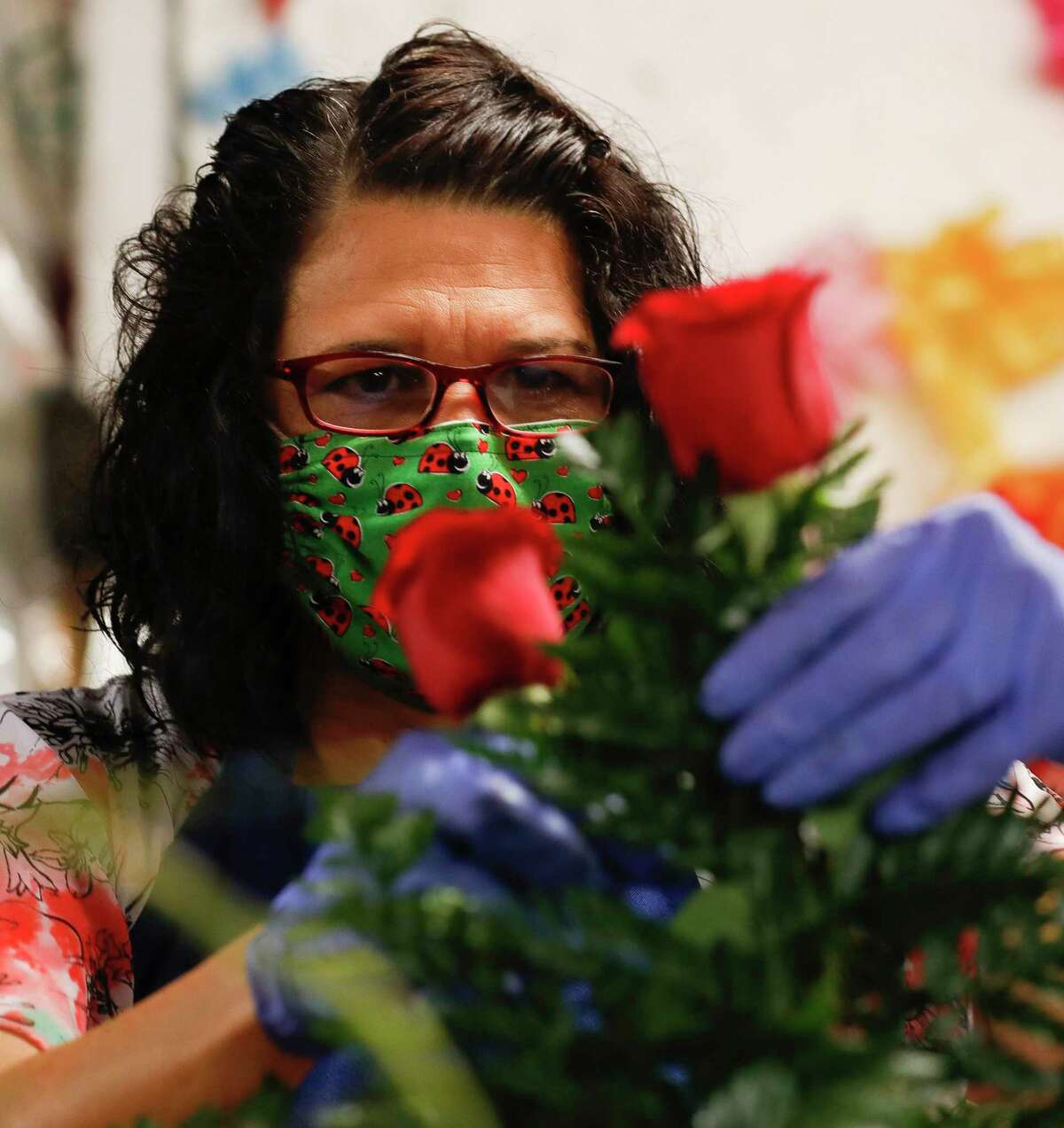 Melissa Vincent places a rose into a funeral arrangement at Heavenly Cakes and Flowers, Friday, April 17, 2020, in Conroe.