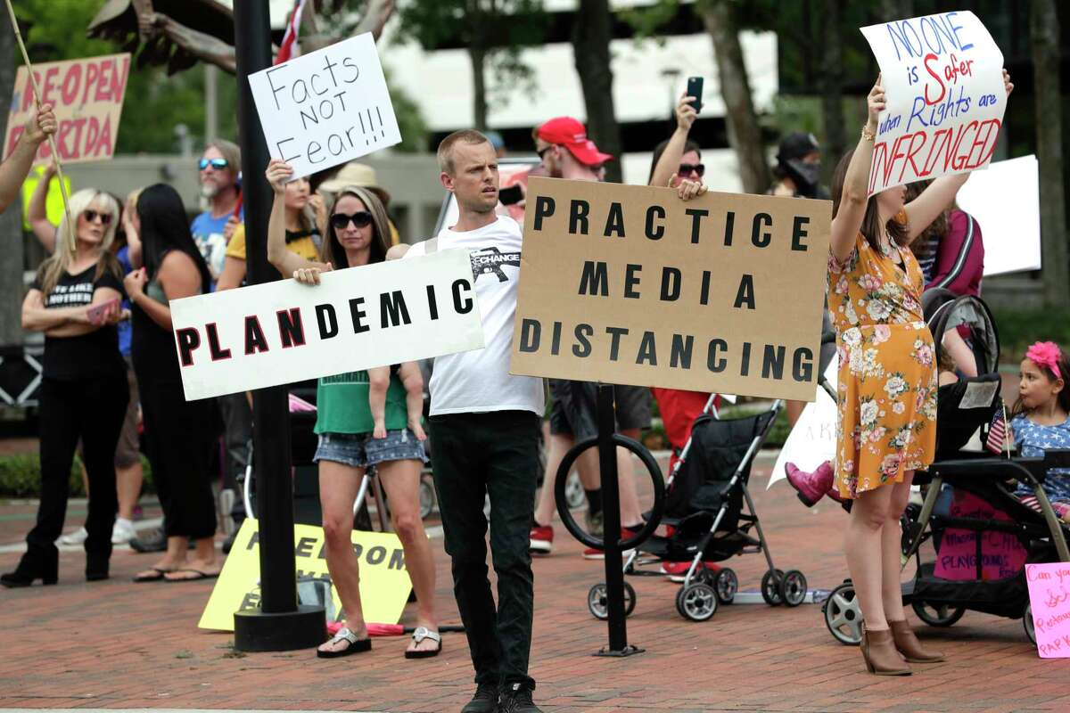 Protesters demanding Florida businesses and government reopen, march in downtown Orlando, Fla., Friday, April 17, 2020. Small-government groups, supporters of President Donald Trump, anti-vaccine advocates, gun rights backers and supporters of right-wing causes have united behind a deep suspicion of efforts to shut down daily life to slow the spread of the coronavirus. (AP Photo/John Raoux)