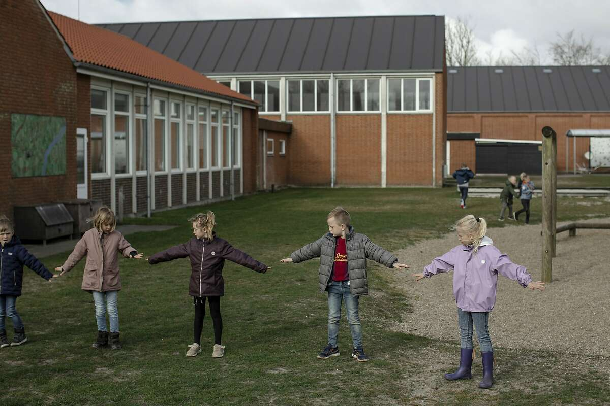Children check their distancing after recess while waiting to go back inside their elementary school in Logumkloster, Denmark, on April 16, 2020. Denmark was the first country in the Western world to reopen its elementary schools since the start of the coronavirus pandemic.