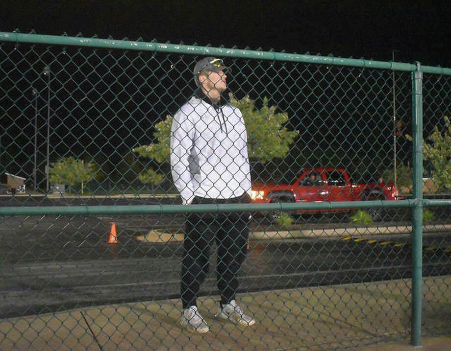 Edwardsville senior Gavin Reames looks at the football field from behind the gate in the parking lot Friday. Reames would have been in the middle of his baseball season. The District 7 Sports Complex was lit up Friday night in honor of the senior class. At 8:20 p.m. (20:20 military time), the lights were turned on for 20 minutes in honor of the seniors, who will end their prep days at home with schools being closed for the remainder of the academic year. A handful of seniors watched from the parking lot a safe distance away from each other. The other Southwestern Conference school, along with many throughout the state, took part in the event. Photo: Matt Kamp|The Intelligencer