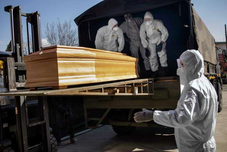 FILE — Members of the Italian army and the Carabinieri load the coffins of coronavirus victims onto a truck in Bergamo, Italy, where the supposed death rate stands at 12.8%, March 24, 2020. Determining what percentage of those infected by the coronavirus will die is a key question for epidemiologists, but an elusive one during the pandemic. (Fabio Bucciarelli/The New York Times)
