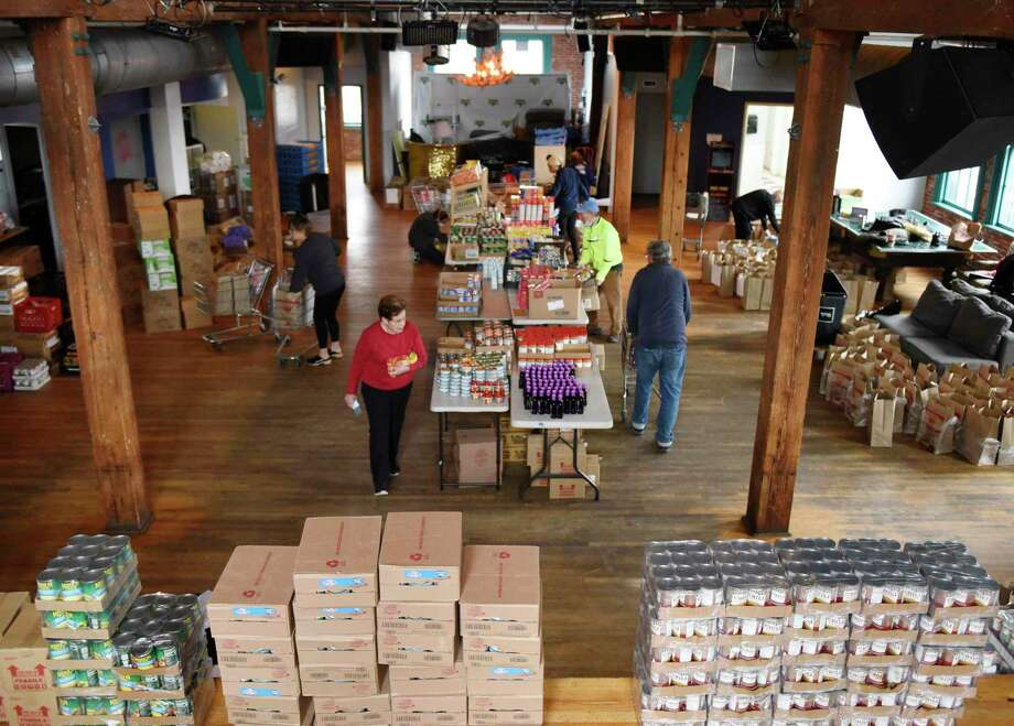 Volunteers work at the new temporary location of Neighbor to Neighbor's food pantry at the Arch Street Teen Center in Greenwich, Conn. Tuesday, March 31, 2020. The Neighbor to Neighbor nonprofit moved its food pantry to the Arch Street Teen Center for a larger workspace that allows for social distancing during the coronavirus outbreak. Photo: Tyler Sizemore / Hearst Connecticut Media / Greenwich Time