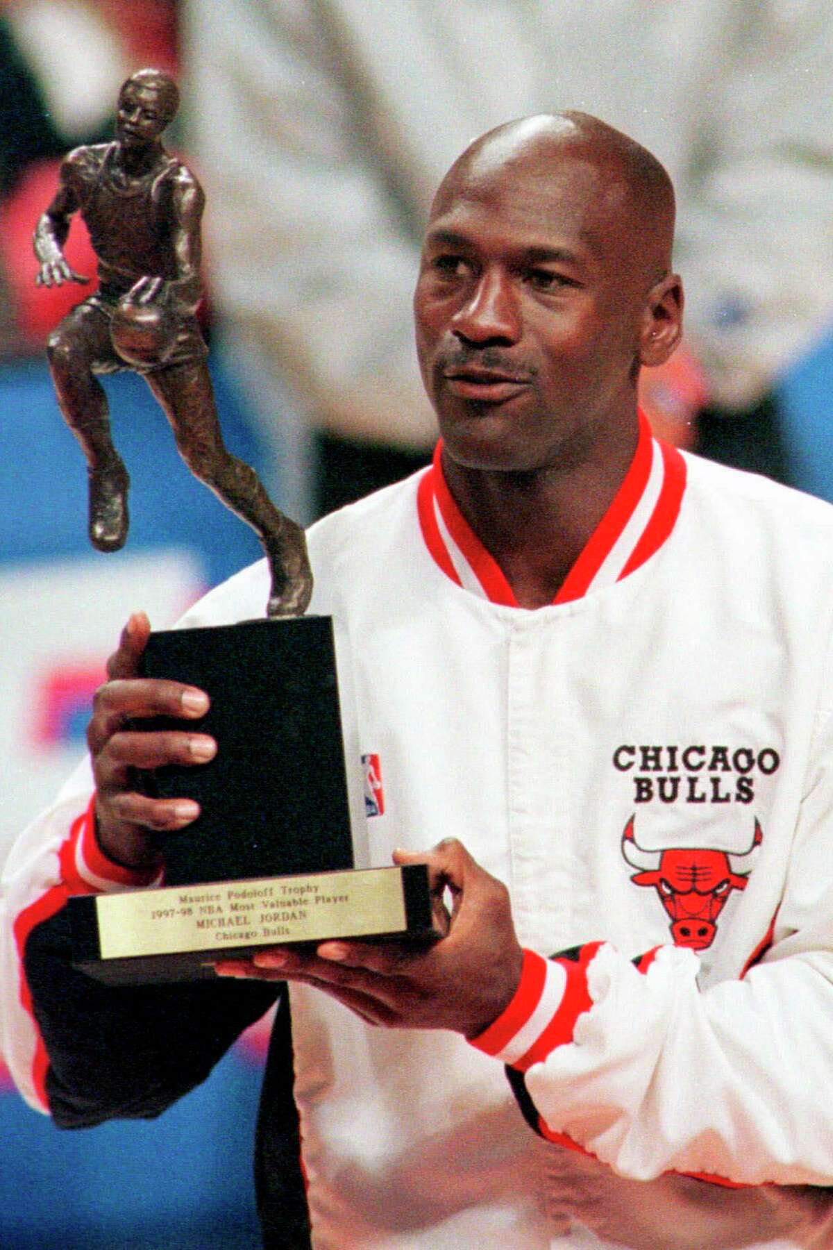 FILE - In this May 19, 1998, file photo, Chicago Bulls' Michael Jordan looks at the MVP award presented to him before the Bulls-Indiana Pacers playoff game in Chicago. Jordan described his final NBA championship season with the Chicago Bulls as a