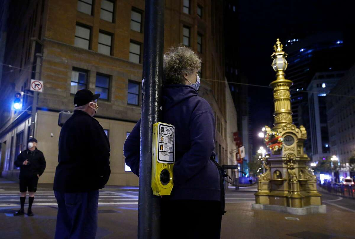 Three people stand apart in front of Lotta's Fountain before dawn for the 114th anniversary of the 1906 earthquake in San Francisco, Calif. on Saturday, April 18, 2020. Normally attended by hundreds, this year's official commemoration was cancelled due to the coronavirus pandemic.