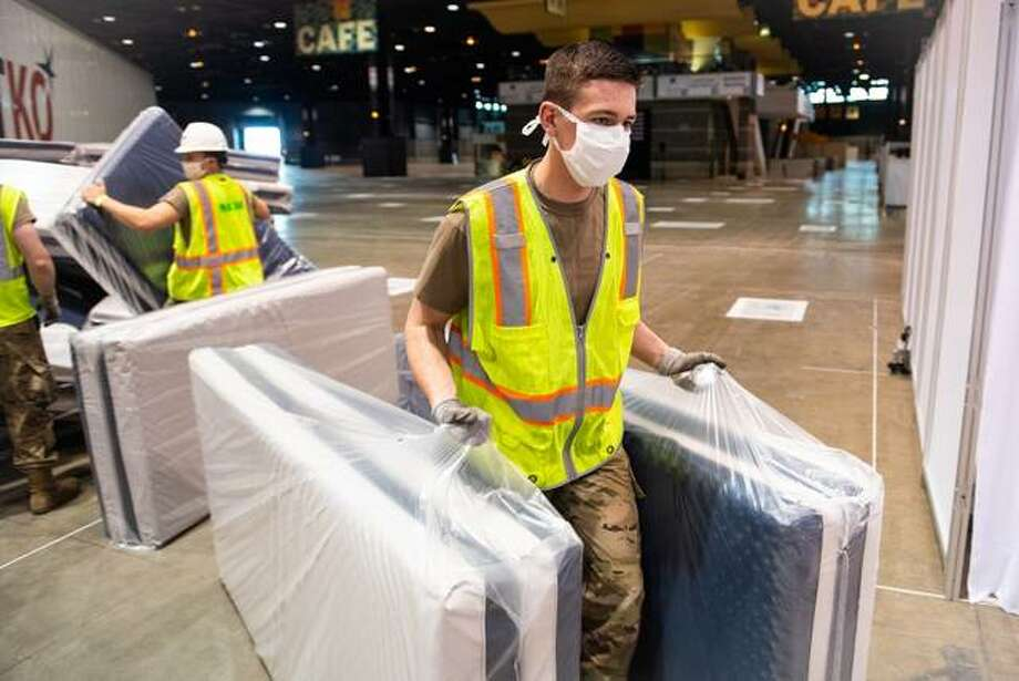 SIUE freshman business student Lucas Maue of Maryville, a member of the Illinois Air National Guard, carries mattresses as he helps set up an Alternate Care Facility in the McCormick Place Convention Center in Chicago.