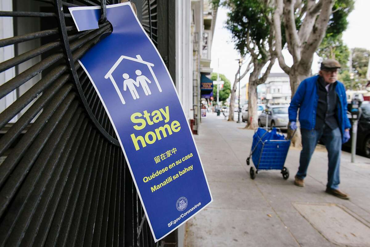 Pedestrians pass by a social distancing sign on a residential gate put up by San Francisco's Latino Task Force on COVID-19 members, in San Francisco, Calif, on Friday, April 17, 2020.